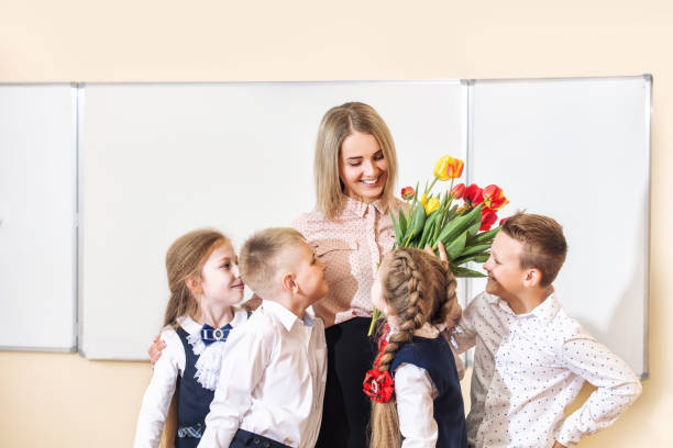 Beautiful children-students together in class at school give flowers to their best woman teacher stock photo
