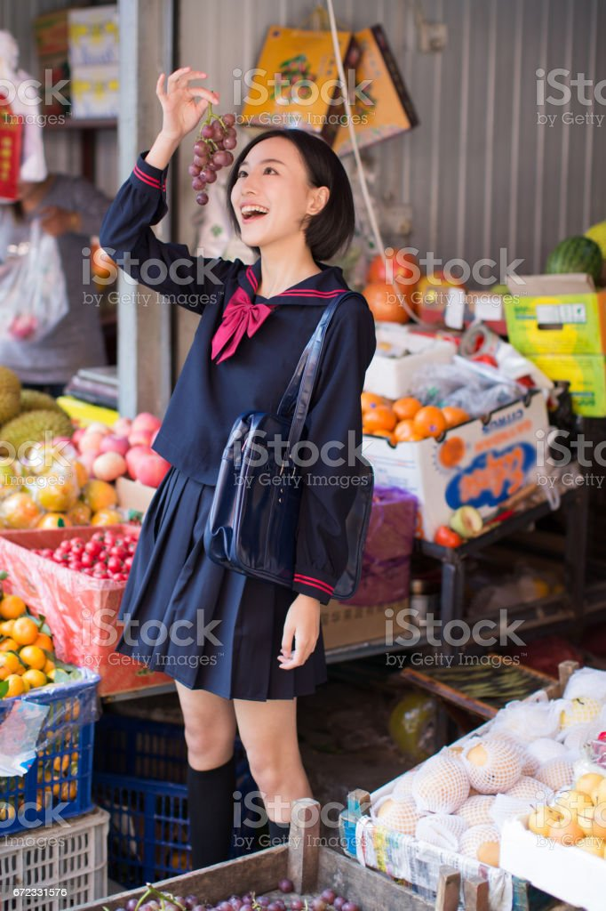 beautiful chinese female students in the market to buy fruit and vegetables stock photo