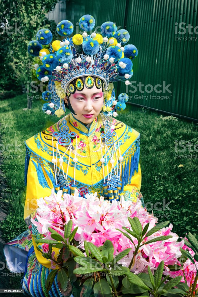 beautiful chinese girl in traditional blue and yellow chinese dress and pompon hat sitting near the pink flower bush stock photo