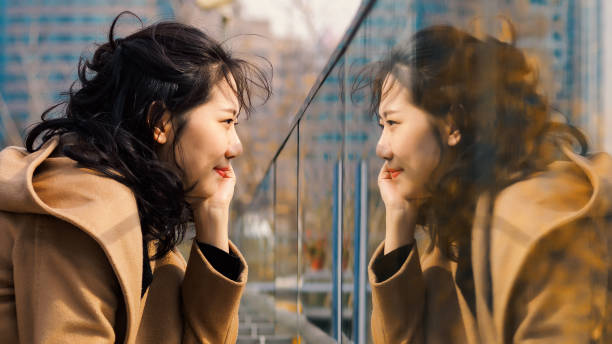 Beautiful Chinese girl looking at her mirror image in glass. stock photo