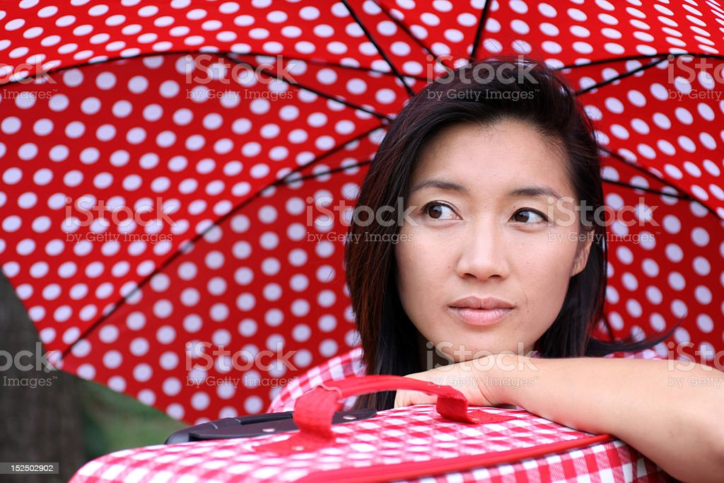 Beautiful Chinese girl with umbrella and suitcase dreaming stock photo