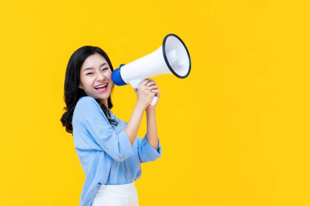 Beautiful Chinese woman cheerfully using magaphone stock photo