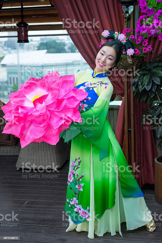 beautiful chinese woman in green traditional dress and floral parasol stock photo