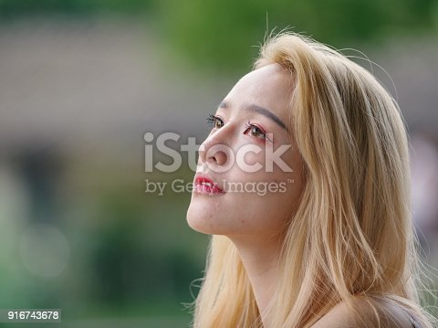 istock Beautiful Chinese young girl wearing a white dress in summer park. Outdoor fashion portrait of glamour young Chinese cheerful stylish lady. Emotions, people, beauty and lifestyle concept. 916743678
