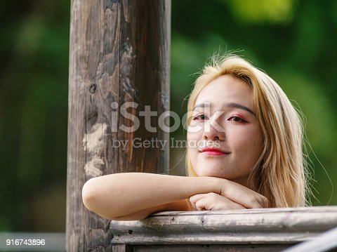 istock Beautiful Chinese young girl wearing a white dress in summer park. Outdoor fashion portrait of glamour young Chinese cheerful stylish lady. Emotions, people, beauty and lifestyle concept. 916743896