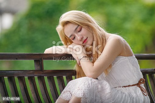 istock Beautiful Chinese young girl wearing a white dress in summer park. Outdoor fashion portrait of glamour young Chinese cheerful stylish lady. Emotions, people, beauty and lifestyle concept. 916746198