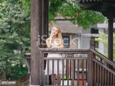istock Beautiful Chinese young girl wearing a white dress in summer park. Outdoor fashion portrait of glamour young Chinese cheerful stylish lady. Emotions, people, beauty and lifestyle concept. 916746466