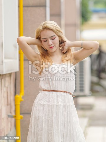 istock Beautiful Chinese young girl wearing a white dress in summer park. Outdoor fashion portrait of glamour young Chinese cheerful stylish lady. Emotions, people, beauty and lifestyle concept. 916746558