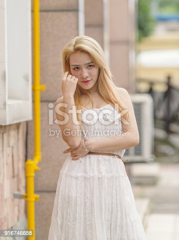 istock Beautiful Chinese young girl wearing a white dress in summer park. Outdoor fashion portrait of glamour young Chinese cheerful stylish lady. Emotions, people, beauty and lifestyle concept. 916746658
