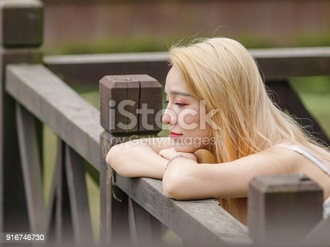 istock Beautiful Chinese young girl wearing a white dress in summer park. Outdoor fashion portrait of glamour young Chinese cheerful stylish lady. Emotions, people, beauty and lifestyle concept. 916746730