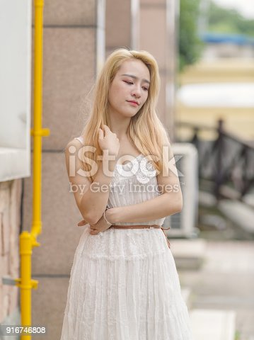 istock Beautiful Chinese young girl wearing a white dress in summer park. Outdoor fashion portrait of glamour young Chinese cheerful stylish lady. Emotions, people, beauty and lifestyle concept. 916746808
