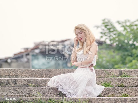 istock Beautiful Chinese young girl wearing a white dress in summer park. Outdoor fashion portrait of glamour young Chinese cheerful stylish lady. Emotions, people, beauty and lifestyle concept. 916746870