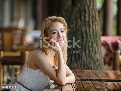 istock Beautiful Chinese young girl wearing a white dress in summer park. Outdoor fashion portrait of glamour young Chinese cheerful stylish lady. Emotions, people, beauty and lifestyle concept. 916747118