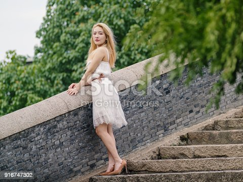 istock Beautiful Chinese young girl wearing a white dress in summer park. Outdoor fashion portrait of glamour young Chinese cheerful stylish lady. Emotions, people, beauty and lifestyle concept. 916747302