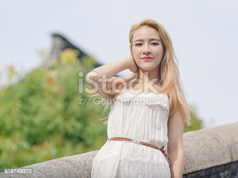 istock Beautiful Chinese young girl wearing a white dress in summer park. Outdoor fashion portrait of glamour young Chinese cheerful stylish lady. Emotions, people, beauty and lifestyle concept. 916749372