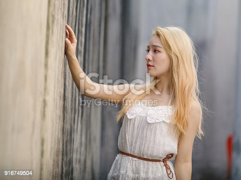 istock Beautiful Chinese young girl wearing a white dress in summer park. Outdoor fashion portrait of glamour young Chinese cheerful stylish lady. Emotions, people, beauty and lifestyle concept. 916749504