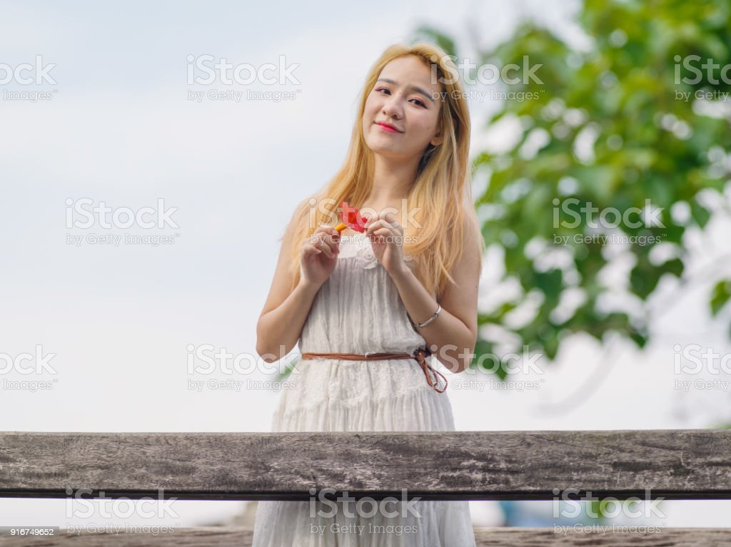 21c5e3c3f Beautiful Chinese young girl wearing a white dress in summer park. Outdoor  fashion portrait of glamour young Chinese cheerful stylish lady.