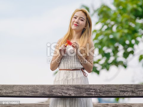istock Beautiful Chinese young girl wearing a white dress in summer park. Outdoor fashion portrait of glamour young Chinese cheerful stylish lady. Emotions, people, beauty and lifestyle concept. 916749652