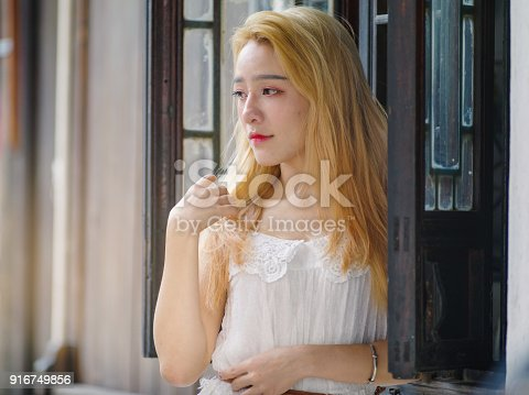 istock Beautiful Chinese young girl wearing a white dress in summer park. Outdoor fashion portrait of glamour young Chinese cheerful stylish lady. Emotions, people, beauty and lifestyle concept. 916749856