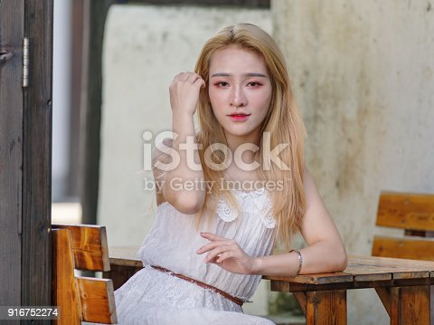 istock Beautiful Chinese young girl wearing a white dress in summer park. Outdoor fashion portrait of glamour young Chinese cheerful stylish lady. Emotions, people, beauty and lifestyle concept. 916752274