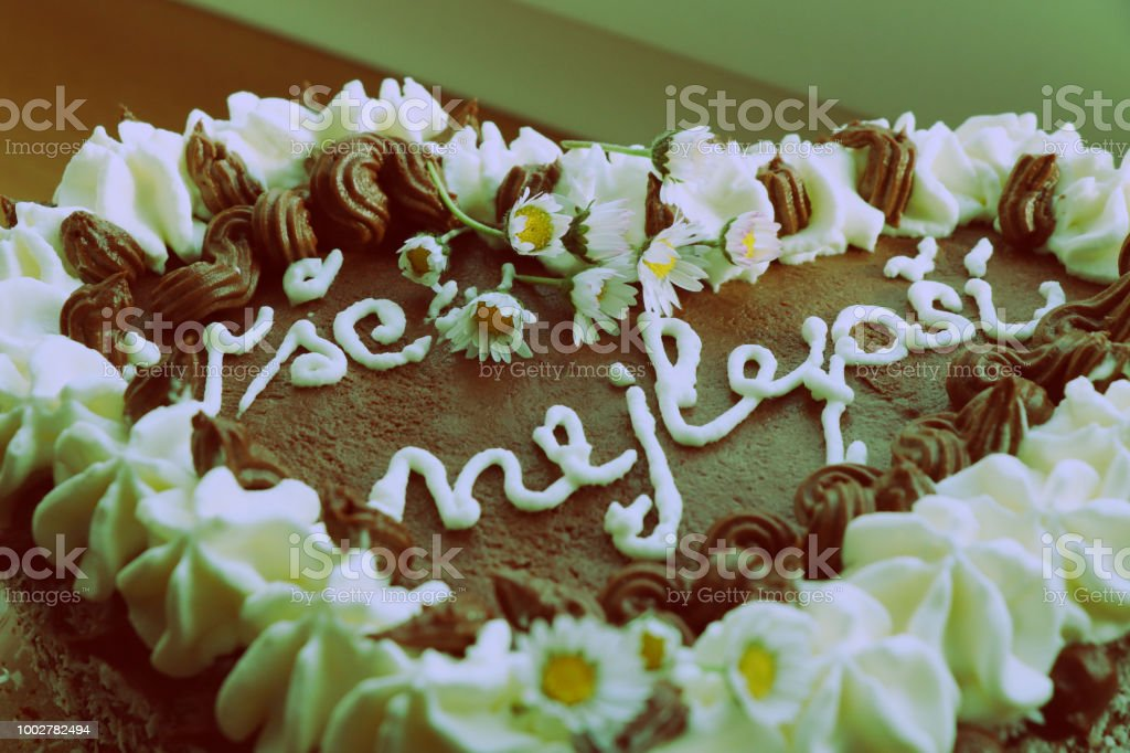 A Beautiful Chocolate Cake With Cream And With Daises As Decoration