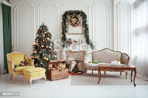 Beautiful Christmas interior. Isolated wreath on wall. New year decoration. Living room with fireplace.