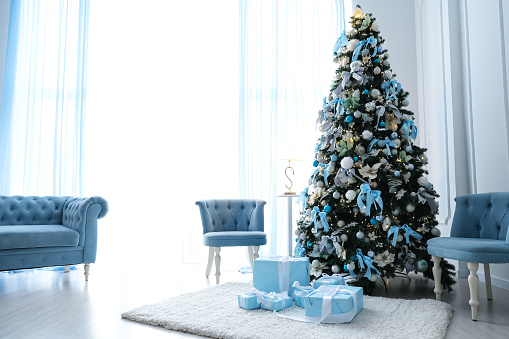 Beautiful Christmas tree with blue decor in a white room.