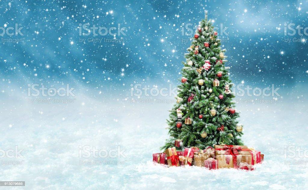 Linda árvore de Natal com dourado e vermelho apresentam caixas em uma paisagem de inverno nevado - foto de acervo