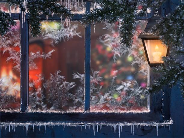 아름 다운 크리스마스 창입니다. 눈, 조명 랜 턴, 차가워요. 창문을 통해 방 벽난로와 크리스마스 트리를 볼 수 있습니다. - 고드름 뉴스 사진 이미지