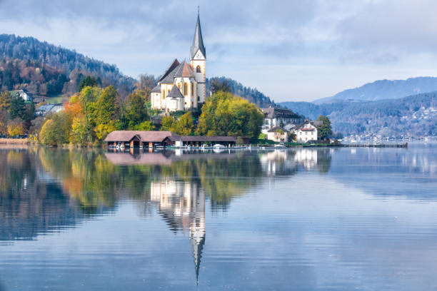 Beautiful church in Augsdorf-Velden, Lake Woerthersee, Carinthia, Austria with majestic reflection on water surface stock photo