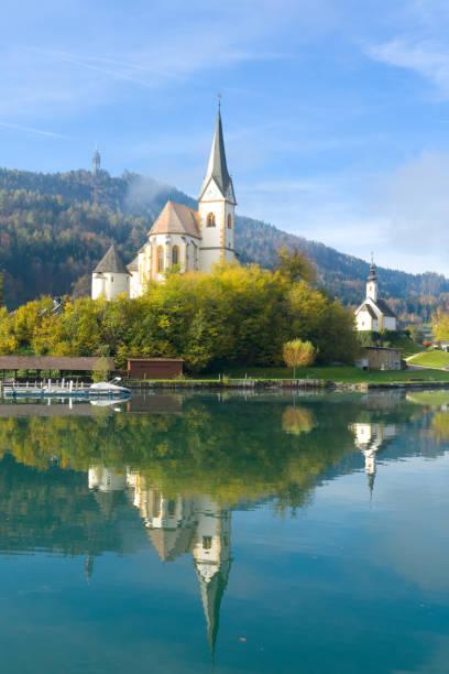 schöne kirche in augsdorf-velden, wörthersee, kärnten, österreich mit majestätischen reflexion über die wasseroberfläche - wörthersee stock-fotos und bilder
