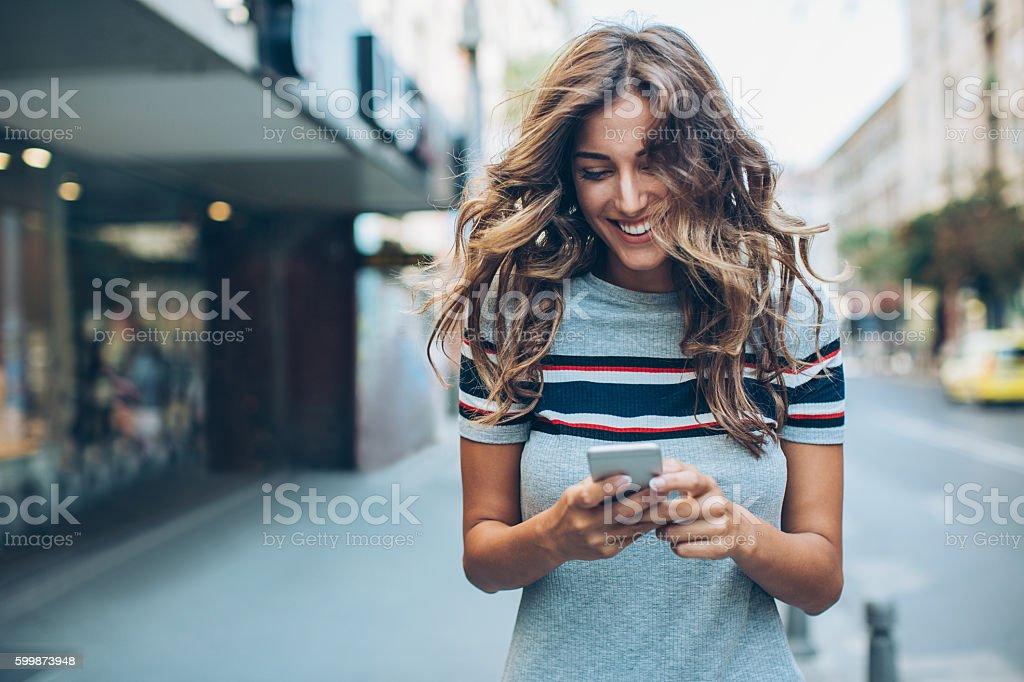 Beautiful city girl texting stock photo