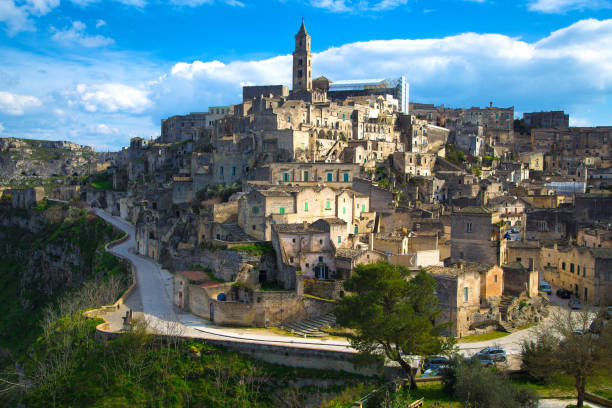 Beautiful cityscape of Matera against the blue sky Beautiful cityscape of Matera against the blue sky. Large white clouds in the sky. City in the rock. The winding road around the city. Green grass and trees. Italy. matera italy stock pictures, royalty-free photos & images