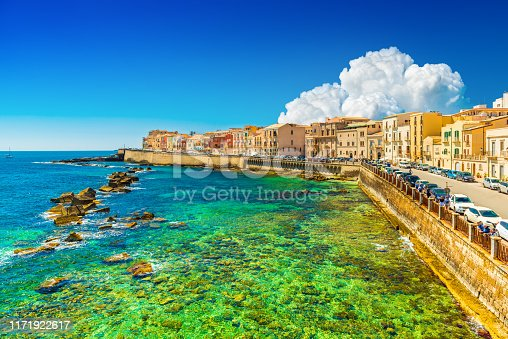 Beautiful cityscape of Ortygia (Ortigia), the historical center of Syracuse, Italy. Skyline of a European coastal town with turquoise transparent water and picturesque clouds in the sky.