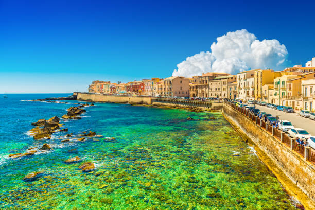 Beautiful cityscape of Ortygia (Ortigia), the historical center of Syracuse, Italy. Skyline of a European coastal town with turquoise transparent water and picturesque clouds in the sky stock photo