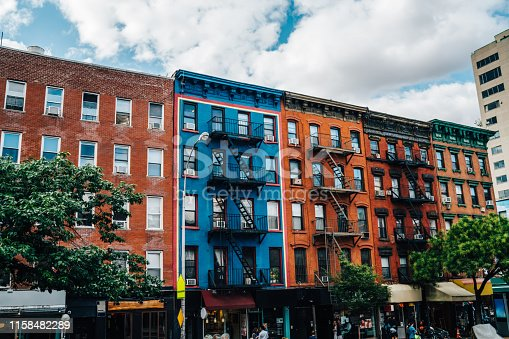 Beautiful cityscape of vintage colourful building with fire escape from residential flats and commercial real estate on ground floor,old houses in Brooklyn district with rental apartments for living