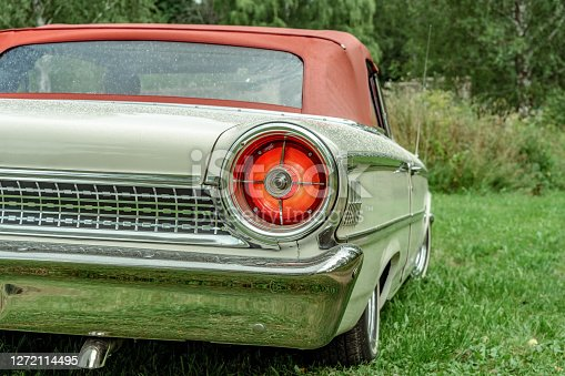 Partial rear view of a classic car from the sixties. White convertible with red top and a large circular tail light
