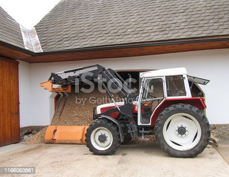 istock Beautiful clean tractor stands near a sawdust with a wood sawdust in a rural yard 1166063861
