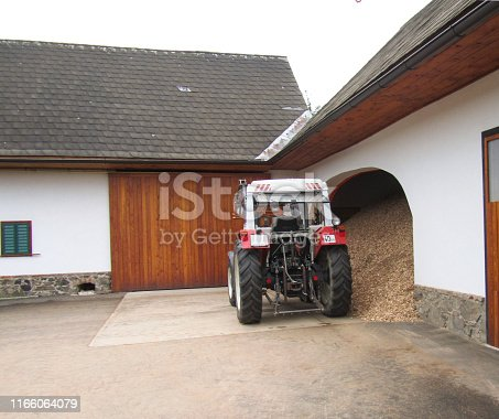 istock A beautiful clean tractor stands near a tiled roof shed in a rural yard 1166064079