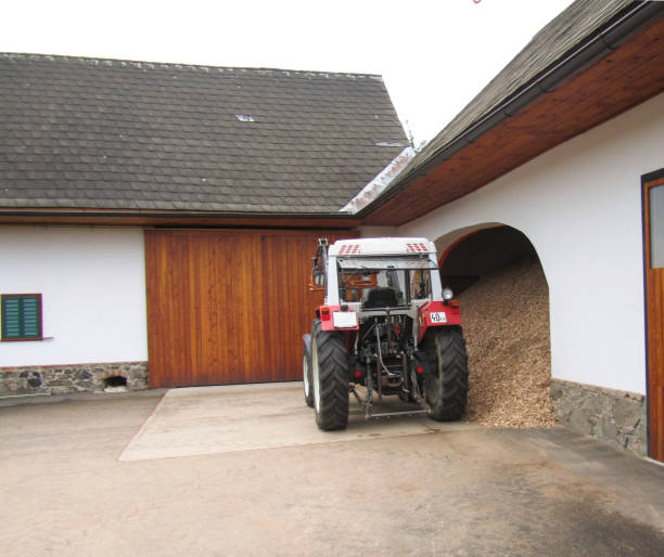 A beautiful clean tractor stands near a tiled roof shed in a rural yard stock photo