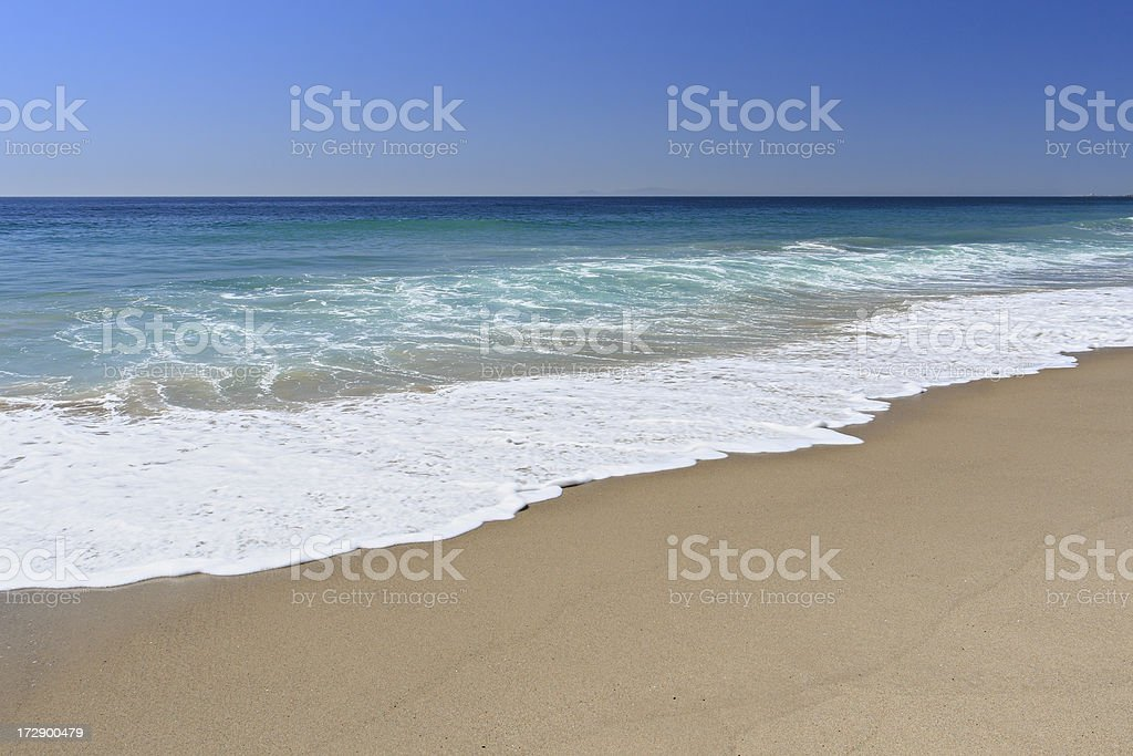 Beautiful clear beach with waves coming to the shoreline stock photo