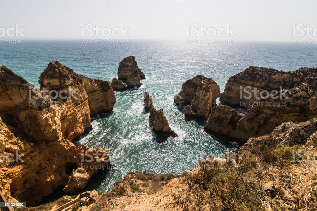 Beautiful cliffs on atlantic coastline with turquoise ocean wave erosion caves background stock photo