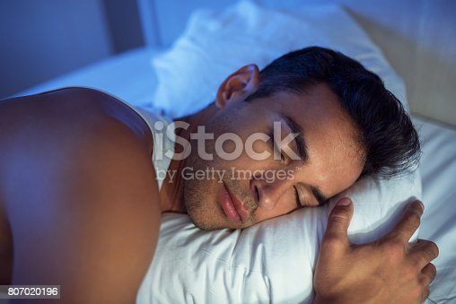istock Beautiful close-up portrait of handsome man on the white bed. 807020196