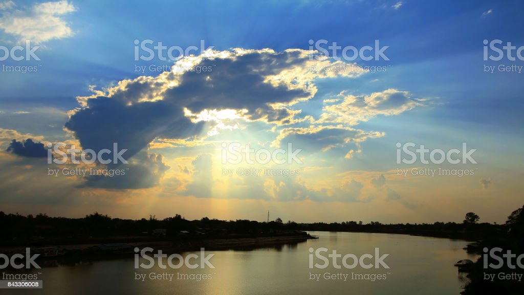 Beautiful cloud formations over river at sunset with sun beams stock photo