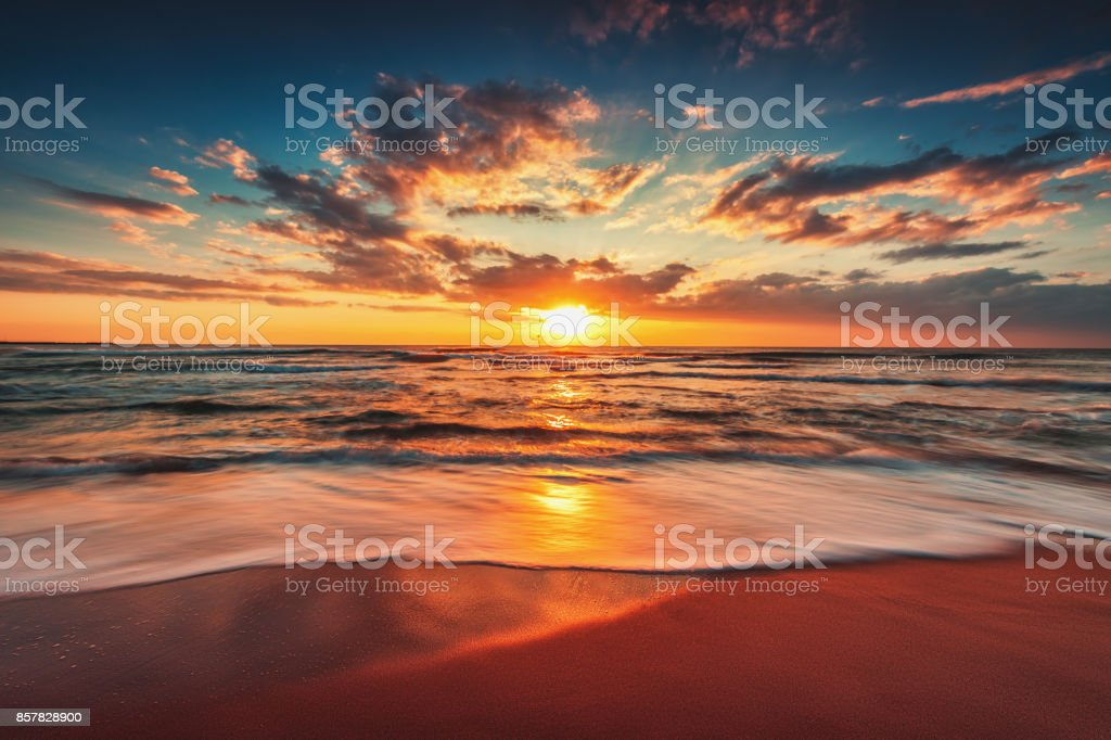 Beautiful cloudscape over the sea and warm sunrise stock photo