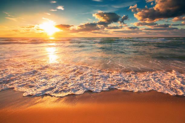 красивый облачный пейзаж над морскими волнами, восход солнца выстрел - sunset стоковые фото и изображения