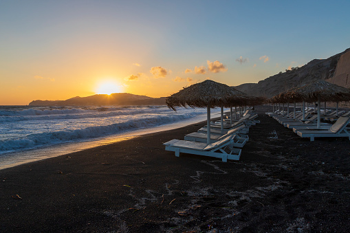 Beautiful coast at sunrise Vlychada beach on Santorini island in Greece. On the background of the sea is a blue sky with the rising sun.