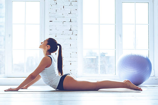 Beautiful cobra. Side view of young beautiful young woman in sportswear doing cobra pose while lying on the floor in front of window at gym cobra pose stock pictures, royalty-free photos & images