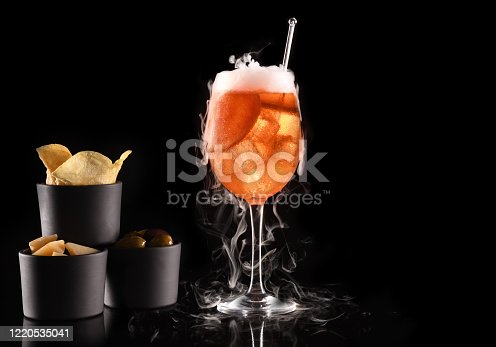 Beautiful cocktail isolated on black background with dry ice smoke. White vapor in cool cold glass, with appetizers and space for copy text. Ideal for bar or celebration concepts like festive days