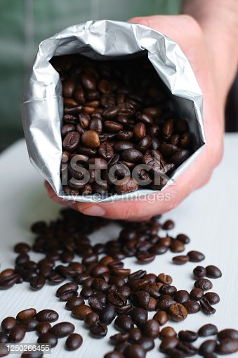 istock Beautiful coffee beans in the hands of a barista. Ready to brew roasted coffee. A man in a culinary apron. Fresh organic coffee. Enjoy the aroma. Making coffee, professional service 1250266455